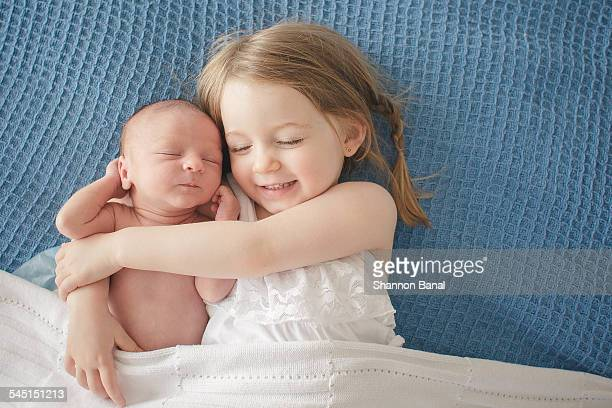 preschool girl hugs newborn baby brother - sister stock photos and pictures