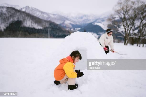 Preschool girl making igloo on snowy field
