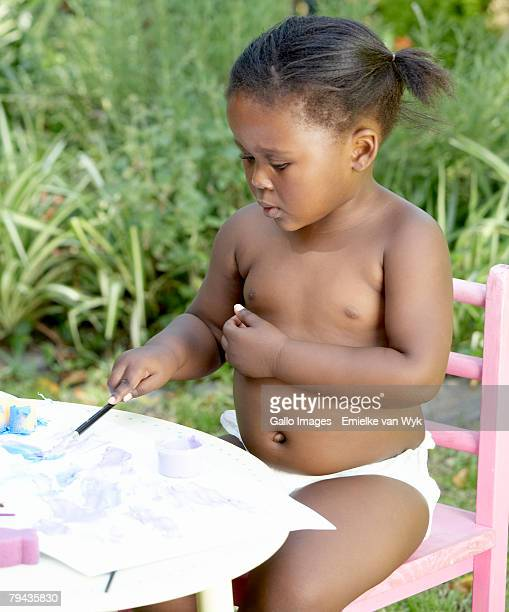Pre-school girl painting outdoors.Cape Town, Western Cape Province, South Africa
