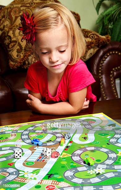 preschool girl playing a board game - game night stock photos and pictures