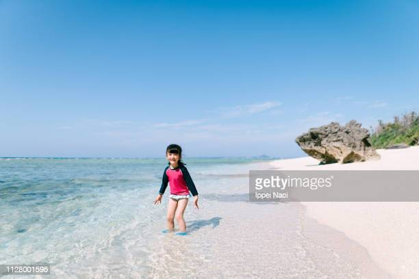 Preschool girl playing in shallow tropical water with white sand beach, Japan