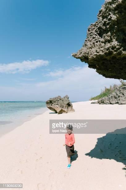 Preschool girl running on tropical beach, Okinawa, Japan