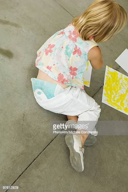 preschool girl sitting on ground painting, high angle view - diaper girl photos et images de collection