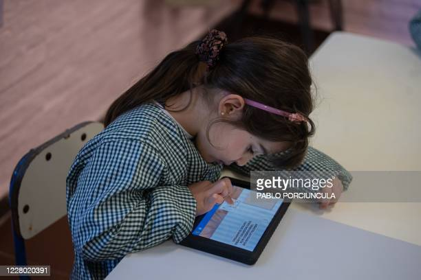 "Pre-school girl uses her ""Ceibalita tablet"" during a class in a public school in Montevideo, amid the COVID-19 novel coronavirus pandemic, on August..."