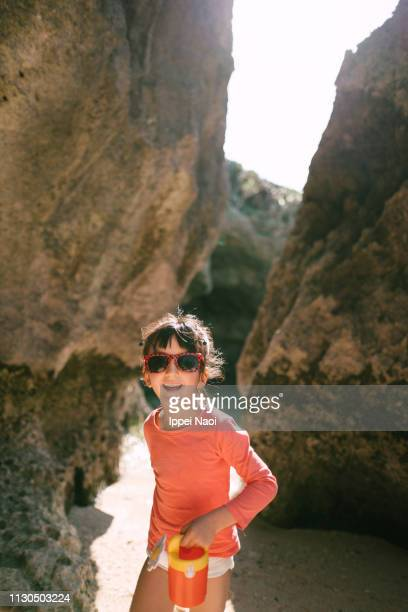 Preschool girl wearing sunglasses and playing on beach in cave, Okinawa, Japan