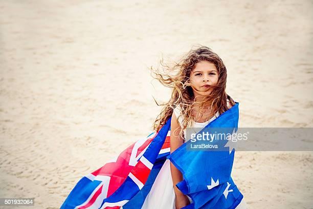 Preschool girl with Australian flag on the beach
