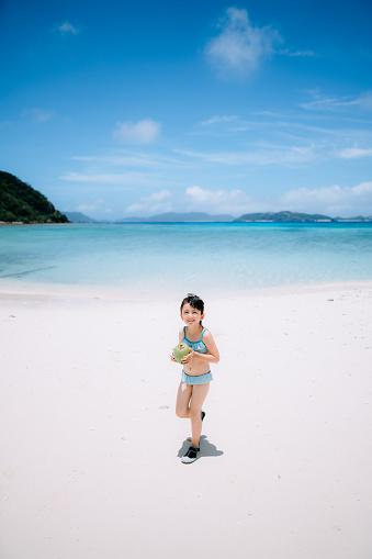 Preschool girl with coconut walking on tropical beach, Okinawa, Japan - gettyimageskorea