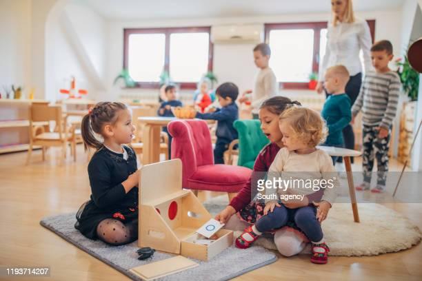 ragazze in età prescolare che giocano in classe prescolare - educazione di scuola materna foto e immagini stock