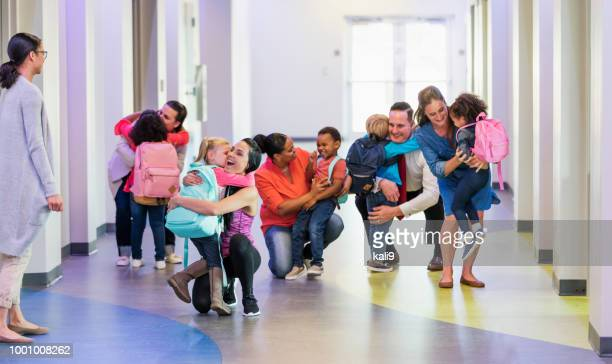 preschool students, parents, hugs on first day of school - sollevare foto e immagini stock