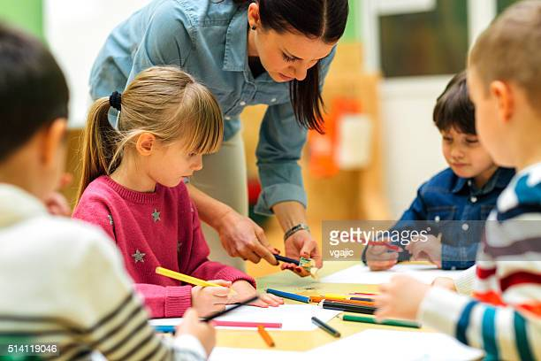 Preschool teacher and children drawing and coloring in their classroom