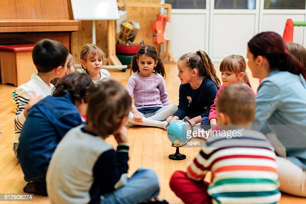 preschool teacher and children in classroom - differential focus stock pictures, royalty-free photos & images