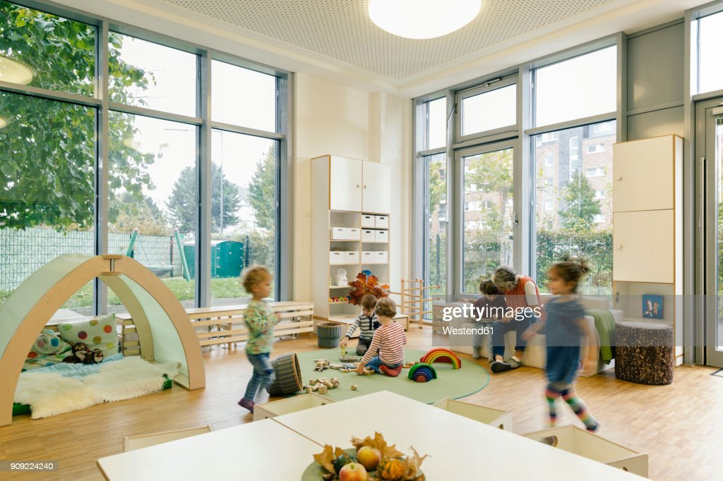 Pre-school teacher and children in playing in learning room in kindergarten : Stock Photo