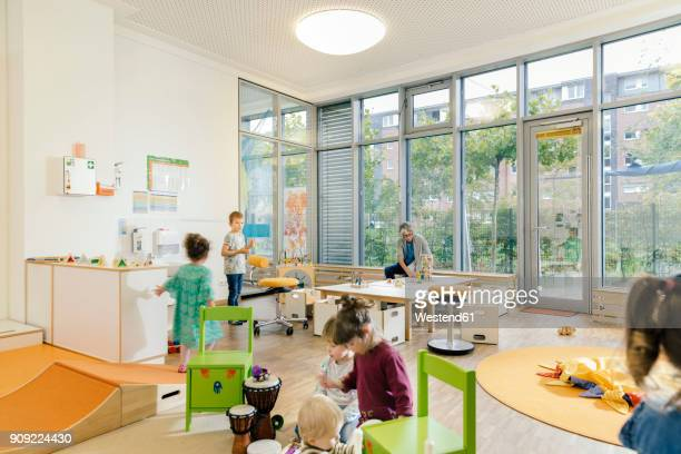 pre-school teacher and children in playing in learning room in kindergarten - kindergarten stock-fotos und bilder