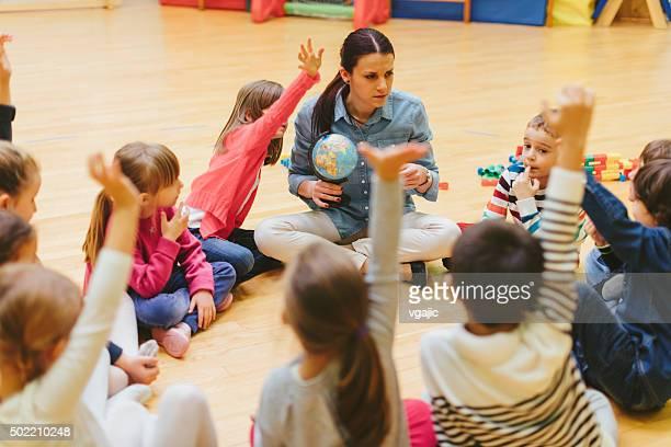 Preschool teacher and children sitting on floor in classroom.