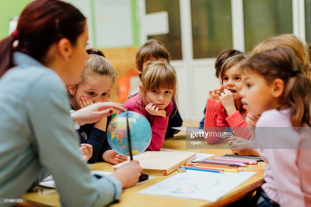 Preschool teacher and children using globe. : Stock Photo