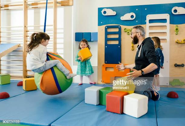 pre-school teacher and happy children playing in gym room in kindergarten - kindergarten stock-fotos und bilder