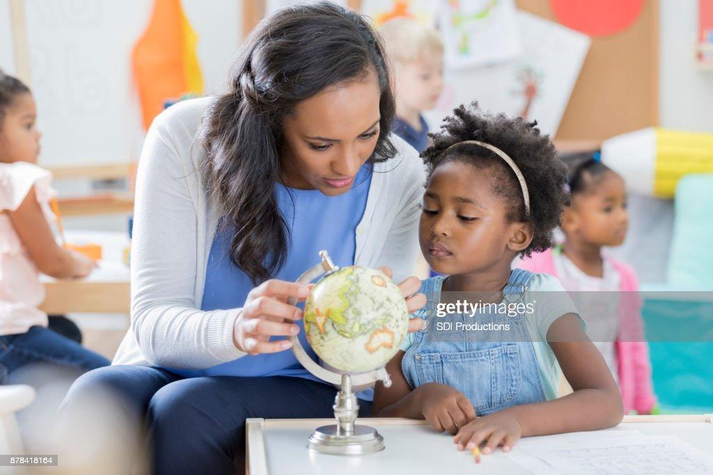 Preschool teacher and student look at globe : Stock Photo