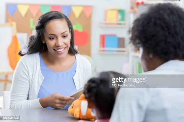 Preschool teacher greets new student and mom