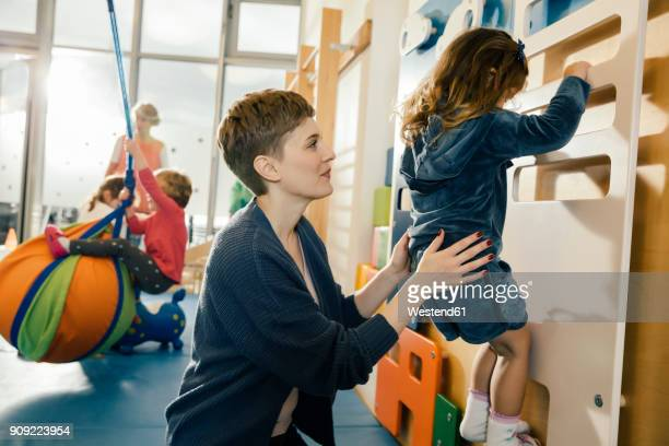 pre-school teacher helping little girl climbing up a wall - aktivitäten und sport stock-fotos und bilder