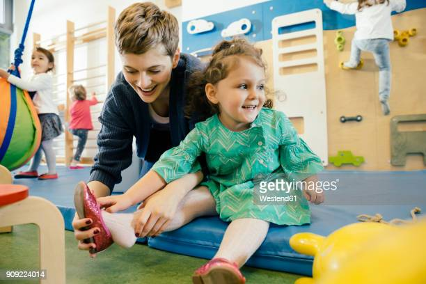 pre-school teacher helping little girl putting a shoe on - vorschulkind stock-fotos und bilder
