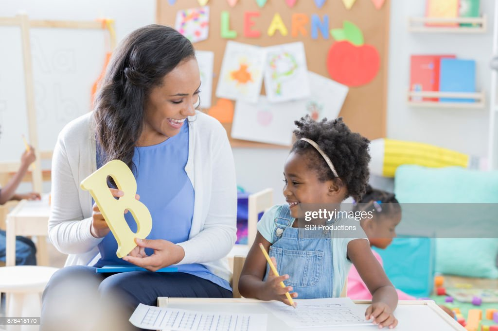 Preschool teacher helps student with alphabet : Stock Photo