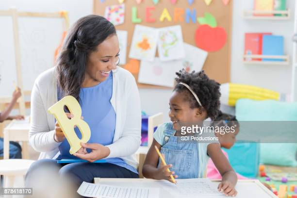 preschool teacher helps student with alphabet - letra b imagens e fotografias de stock