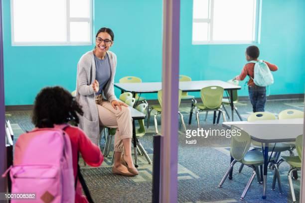 Preschool teacher in classroom greeting student