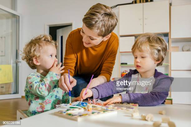 pre-school teacher painting with two children in kindergarten - kindergarten stock-fotos und bilder