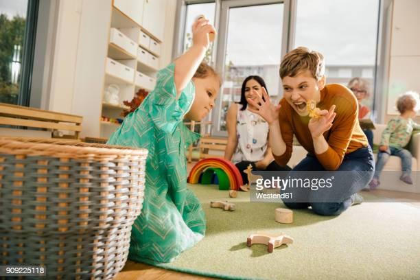 Pre-school teacher playing with girl in kindergarten