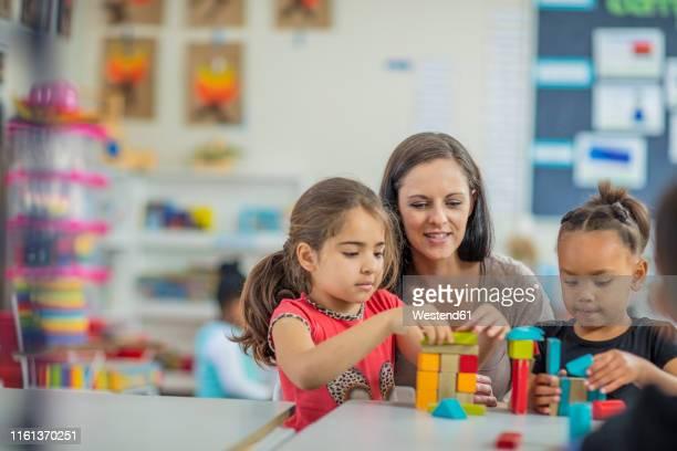 pre-school teacher playing with girls in kindergarten - servizi per l'infanzia foto e immagini stock