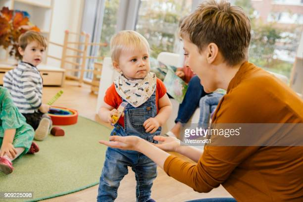 Pre-school teacher playing with little boy in kindergarten