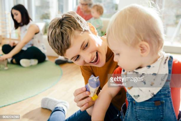 pre-school teacher playing with toddler in kindergarten - kindergarten stock-fotos und bilder