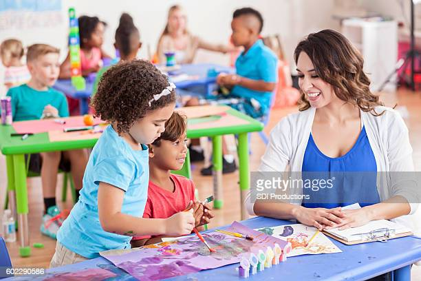 Preschool teacher plays with two students painting a picture