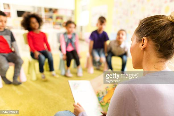 Preschool teacher reading a story to children at kindergarten.