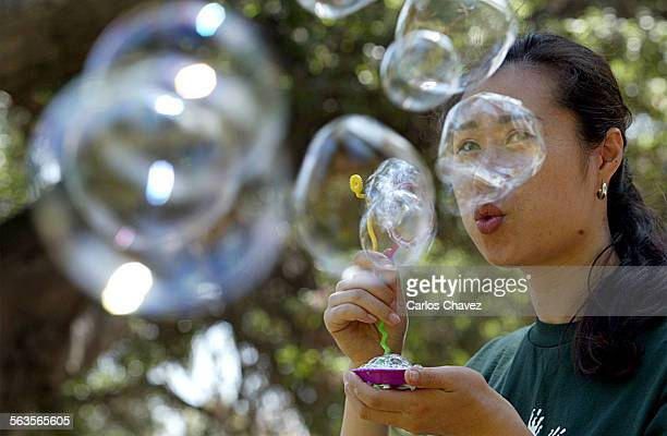 Preschool teacher Shanell Kim blows bubbles for her student at Griffith Park on a warm Wednesday afternoon