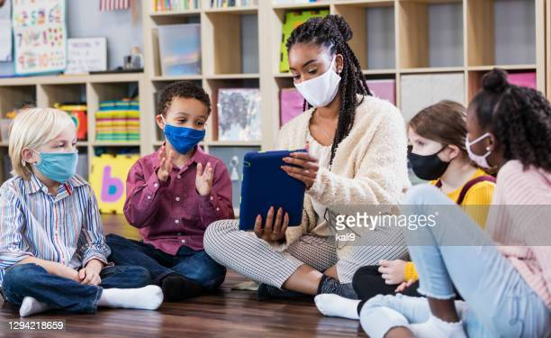 preschool teacher, students in class, wearing masks - teacher stock pictures, royalty-free photos & images