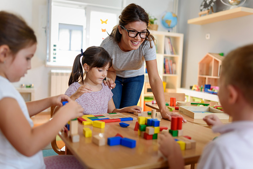 Preschool teacher with children playing with didactic toys 1044044044