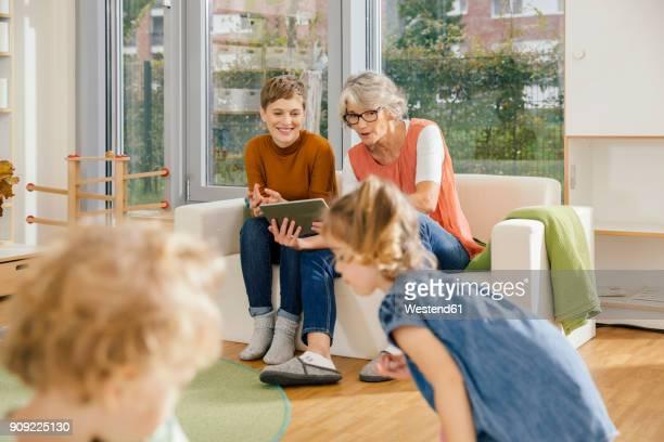 Pre-school teachers with tablet looking at children in kindergarten