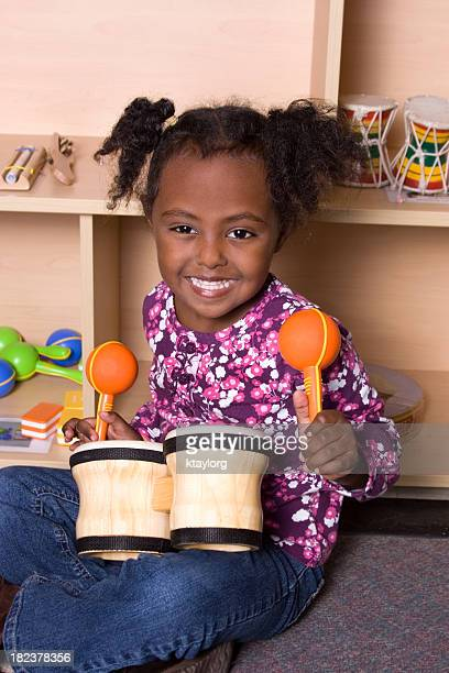 preschooler at music station in school - maraca stock photos and pictures