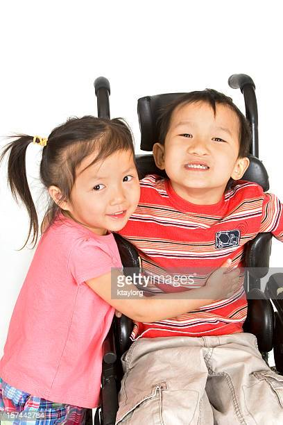 Criança Pré-escolar agarrar o seu amigo em Cadeira de Rodas