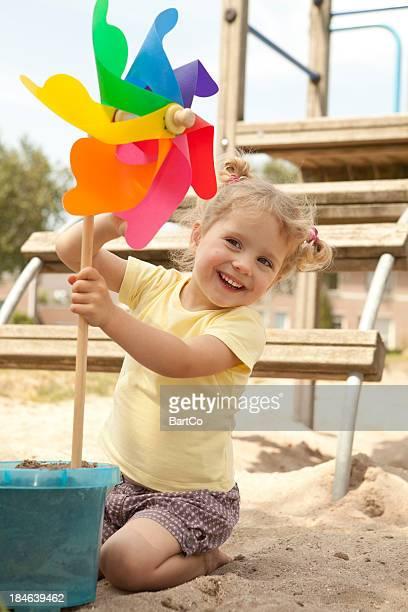 Preschooler looking at toy in sandbox.