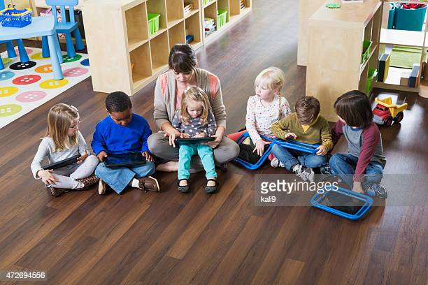 Preschoolers and teacher with digital tablets in class
