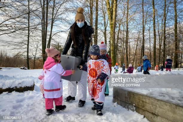 Preschoolers and their teacher Eve move the ballot box for vote counting operations on January 18, 2021 in Lausanne during a referendum, organized by...