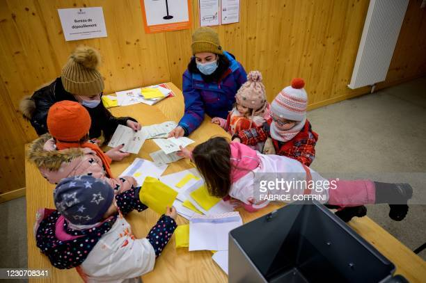 Preschoolers and their teachers perform vote counting operations on January 18, 2021 in Lausanne during a referendum, organized by private preschools...
