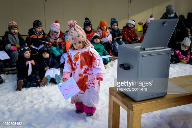 Preschoolers are seen next to the ballot box on January 18, 2021 in Lausanne during a referendum, organized by private preschools network Educalis,...