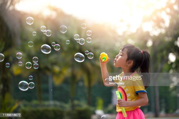 preschoolers girl soap bubble play time. - bubble stock pictures, royalty-free photos & images