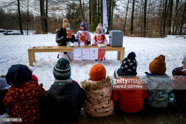 Preschoolers listen the instructions from their teacher Eve prior to place their vote in the ballot box on January 18, 2021 in Lausanne during a...