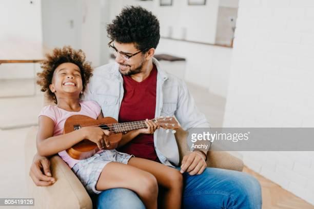 preschoolg girl making a funny face while playing ukulele - ukulele stock pictures, royalty-free photos & images