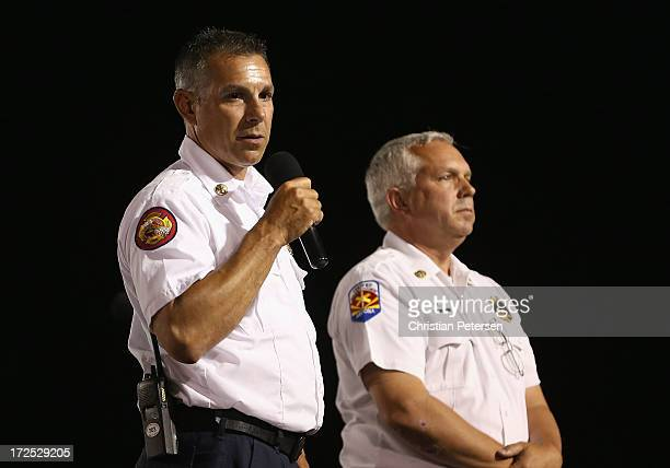 Prescott Fire Battalion Chief Ralph Lucas speaks alongside Don Devendorf on stage at the candlelight vigil in honor of the 19 fallen firefighters at...