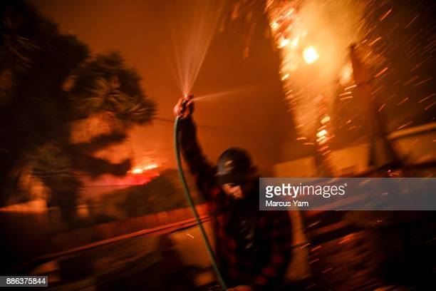 Prescott McKenzie hoses down the roof as embers move with the wind during a brush fire on December 5 2017 in Ventura California